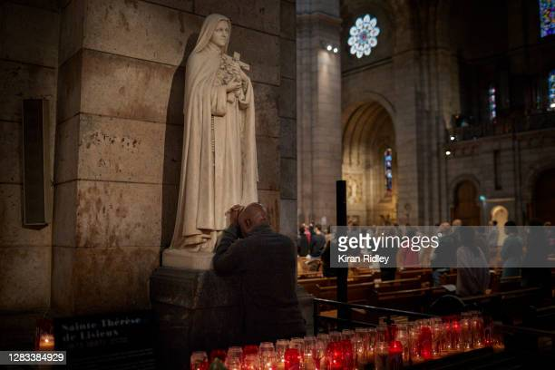 A man prays in front of a Statue of St Thérèse of Lisieux inside Sacré Cœur Basilica in Montmartre Paris on All Saints Day on November 01 2020 in...