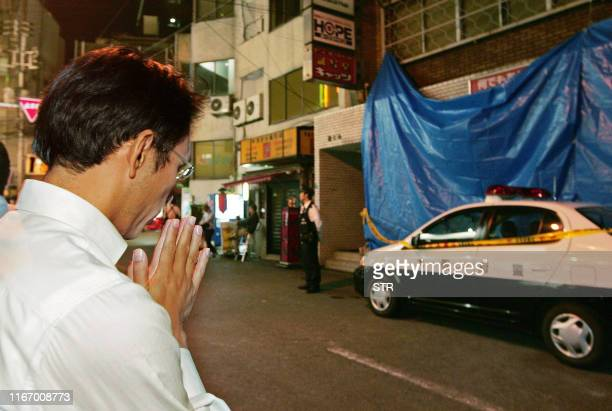A man prays in front of a video shop covered with blue sheet in central Osaka western Japan on October 1 2008 A fire broke out in the video shop...