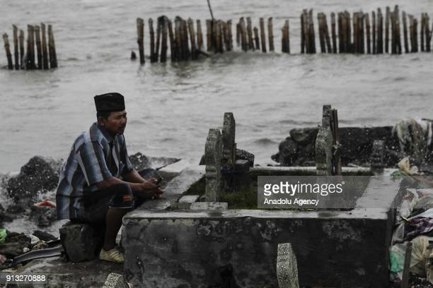 A man prays in front of graves which are inundated by trash following the rising of sea level in Tambak Lorok village of Semarang Central Java...