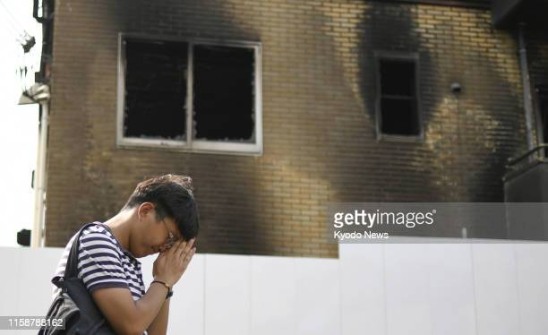 A man prays in front of the burntout threestory studio of Kyoto Animation Co in Kyoto on July 31 about two weeks after an arson attack that killed 35...