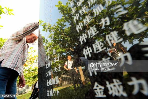 A man prays in front of the Cornerstone of Peace where the names of their bereaved family members and relatives engraved at the Peace Memorial Park...