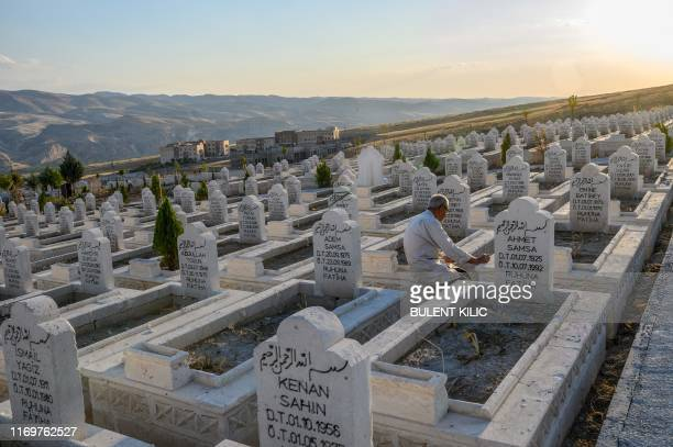 A man prays in the new Hasankeyf cemetery where bodies have been moved to from the old Hasankeyf cemetery on the banks of the Tigris in southeastern...