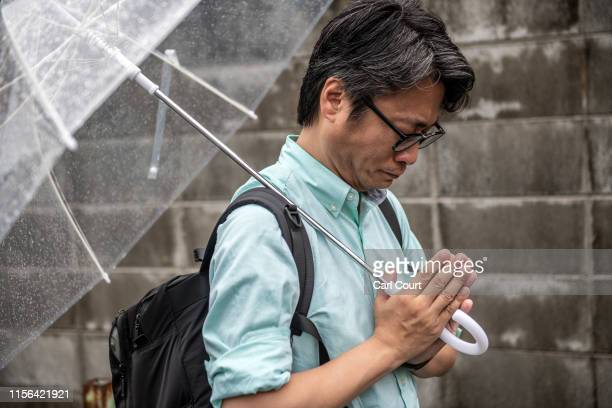 A man prays near the Kyoto Animation Co studio building after it was attacked by an arsonist on July 19 2019 in Kyoto Japan Thirty three people are...