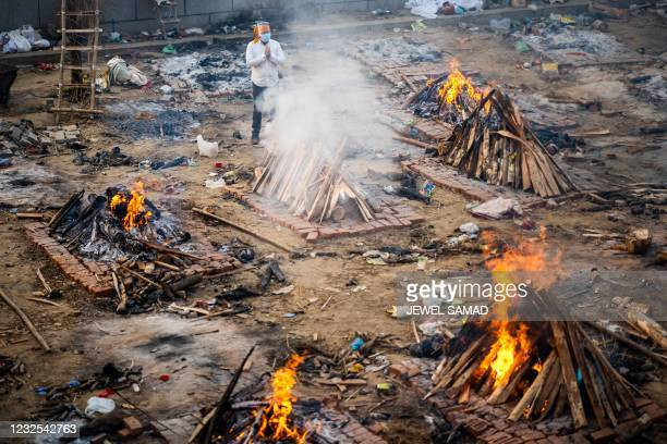 Man prays next to a burning pyre of a victim who died of the Covid-19 coronavirus at a cremation ground in New Delhi on April 26, 2021.