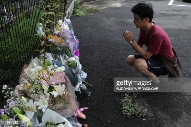 A man prays next to flowers and tributes laid at the scene where over 30 people died in a fire at the Kyoto Animation company building in Kyoto on...