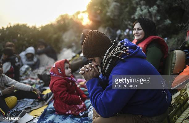 A man prays next to other migrants and refugees as they wait for the night to fall to try to cross to the Greek island of Kos from Bodrum in the...