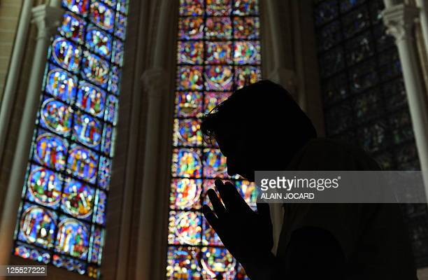 A man prays on August 26 in one of the three restored chapels in the 13th century Cathedral of Chartres western France Considered one of the finest...