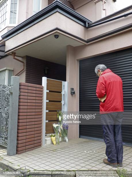 A man prays on March 30 in front of the home of veteran Japanese comedian Ken Shimura who died of pneumonia caused by the novel coronavirus the...