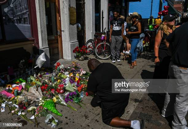 A man prays outside Ned Peppers Bar in the city's historic Oregon District where mass shooter Connor Betts used an AR15like rifle to kill nine people...