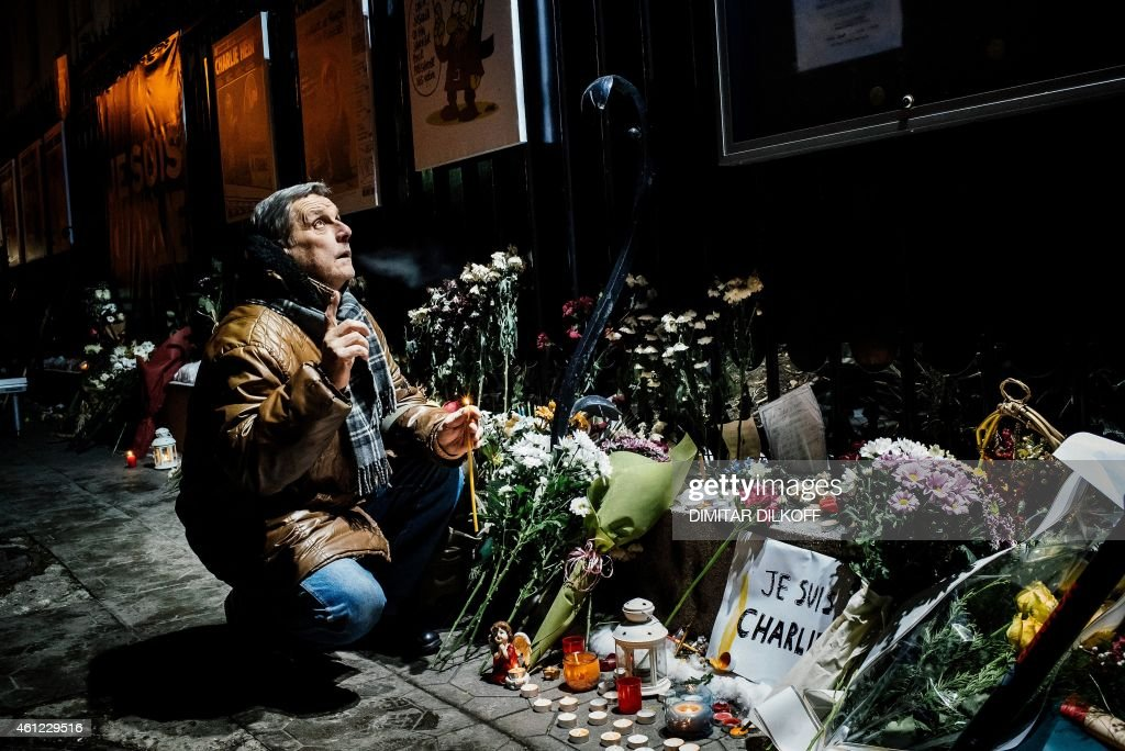 A man prays outside the French Embassy in Sofia on January 9, 2015, to pay homage to the victims of a deadly attack two days prior on the Paris headquarters of French satirical weekly Charlie Hebdo. Elite commandos on January 9 units killed the two suspects in the Charlie Hebdo massacre during a simultaneous assault on the building they were holed up in and on a Paris Jewish supermarket, freeing hostages at both sites.