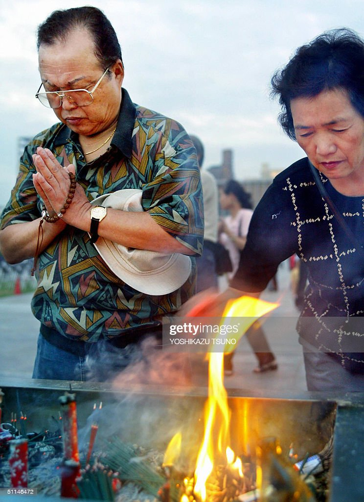 A man prays while his wife burns incense in front of an altar of the memorial monument for the A-bomb victims at the peace Memorial Park in Hiroshima, western Japan 06 August 2004. The 59th memorial service for the two hundred thousand A-bomb victims was held in Hiroshima. AFP PHOTO / Yoshikazu TSUNO