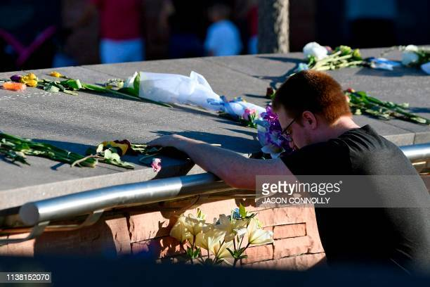 A man prays while visiting the Columbine Memorial at Clement Park in Littleton Colorado before a community vigil for the 20th anniversary of the...