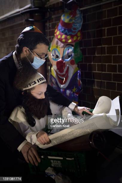Man prays with a child in front of a clown-mask during an open-air religious service to celebrate the beginning of the Jewish festive holiday of...