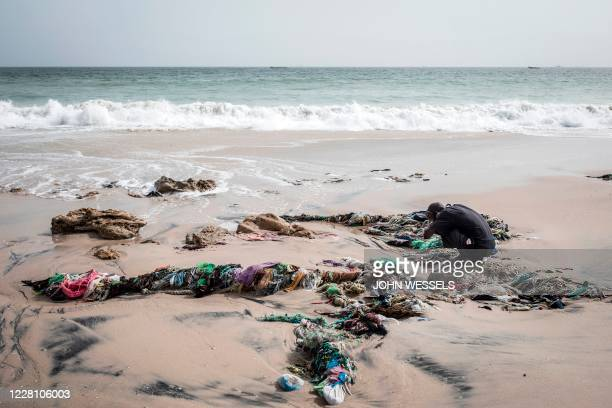 Man preforms his ablutions before evening prayers along the coastline in Bargny on July 06, 2020. - The coastline of Bargny is well known for being...