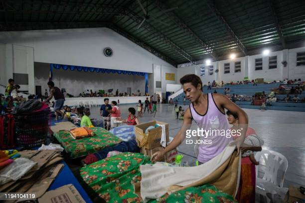 A man prepares a bed for his family members at an evacuation centre for people displaced by the eruption of the Taal volcano at the La Consolacion...