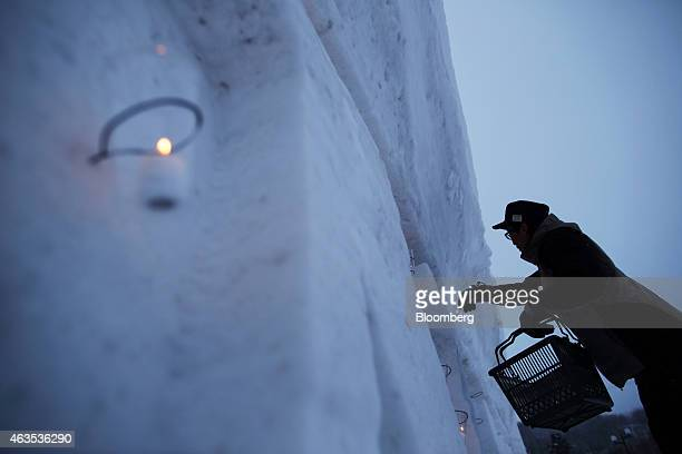 A man prepares a candle on a snow statue before an event in the Hirafu area of Kutchan Hokkaido Japan on Saturday Feb 14 2015 Japan had a record...