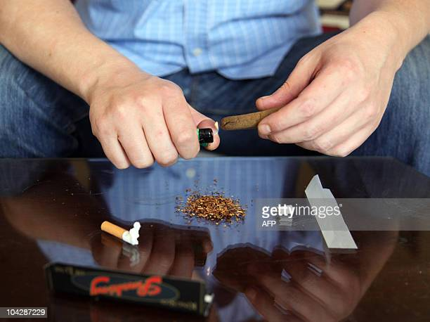 A man prepares a hashish joint at his home in Cairo on April 4 2010 Egypt's market for the illegal drug hashish is going through a shortage that is...
