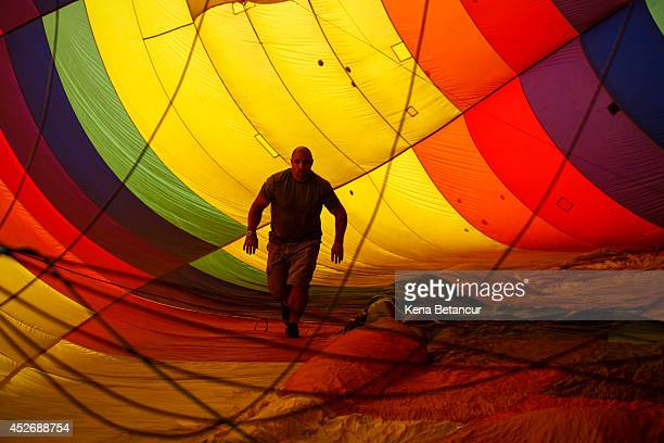 A man prepares a hot air balloon during the 32nd annual QuickChek New Jersey Festival of Ballooning on July 25 2014 in Readington New Jersey The...