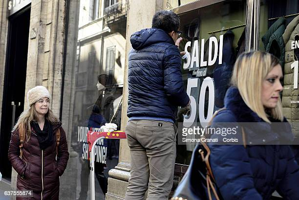 A man prepares a shop window that indicates 'sales' in Via del Corso on January 4 2016 in Rome Italy The winter sales begin in Rome tomorrow on...