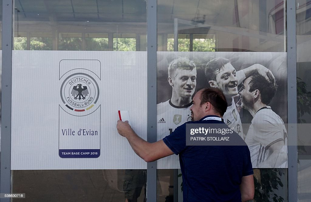 A man prepares a wall at the press centre of Germany's team at their training grounds in Evian-les-Bains, central-eastern France, on June 7, 2016, three days ahead of the Euro 2016 football tournament. / AFP / PATRIK