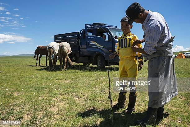 A man prepares a young rider prior to a horse race during the traditionnal Nadaam festival in a nomad camp in the Ovorkhangai province on July 18...