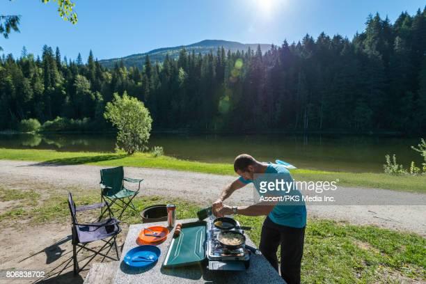 Man prepares camping breakfast beside beautiful mountain lake