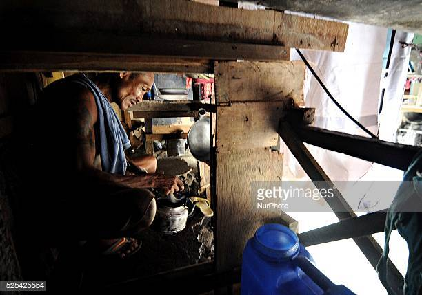 A man prepares coffee inside his makeshift home under a busy bridge in Quezon city suburban Manila Philippines July 30 2013 Photo Ezra Acayan/NurPhoto