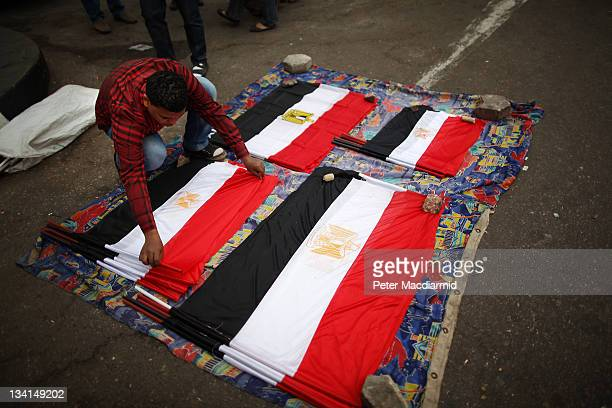 A man prepares flags for sale at an entrance to Tahrir Square on November 27 2011 in Cairo Egypt Protestors are continuing to occupy Tahrir Square...