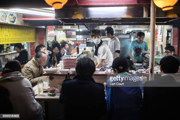 A man prepares food as customers eat at a restaurant in Omoide Yokocho a narrow lane of mainly yakitori grills and food stalls that is known locally...