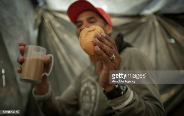 Man prepares his breakfast in his small tent at gigantic terrain invaded by homeless workers linked to the Homeless Workers Movement in Sao Bernardo...