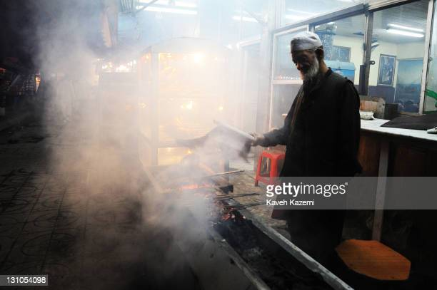 Man prepares kebabs on charcoal grill outside a restaurant in the early hours of evening on October 16, 2011 in Kabul, Afghanistan.