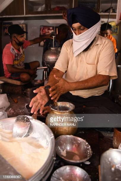 Man prepares Lassi, a traditional blend of yogurt, water and spices, amid rising temperatures during a hot summer day in Amritsar on June 10, 2021.