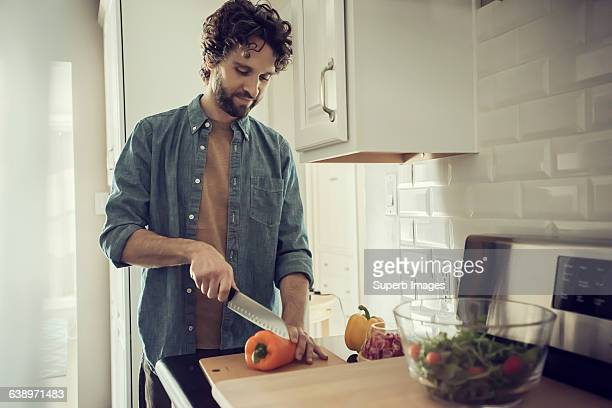 man prepares meal in kitchen - cutting stock pictures, royalty-free photos & images