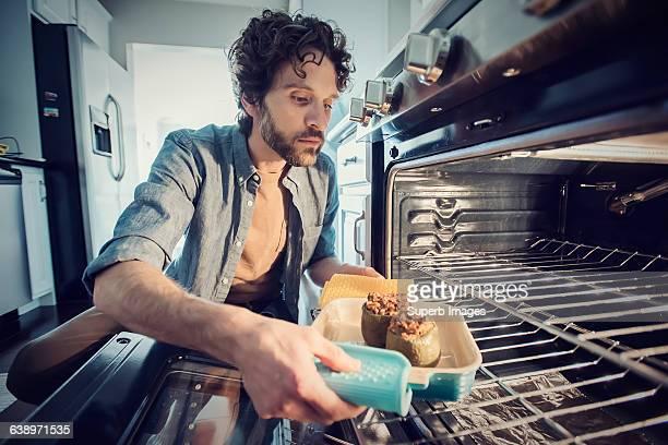 man prepares meal in kitchen - cuisine non professionnelle photos et images de collection