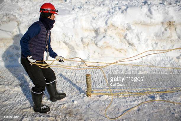 A man prepares rope for use in the construction of the shrine during preparations for the Nozawaonsen Dosojin Fire Festival on January 14 2018 in...