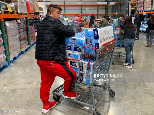 A man prepares to buy 150 rolls of toilet paper at a store as people begin to panic buy and stockpile essentials from fear that supplies will be...