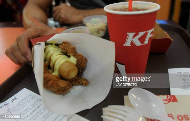 A man prepares to eat a 'Double Down Dog' in Manila on February 3 a product conceived and introduced by the Philippine franchise of KFC Fastfood...