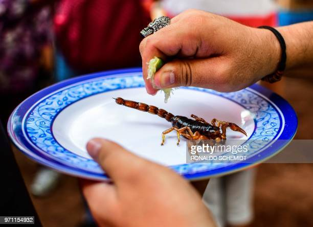 A man prepares to eat a scorpion at a market in Mexico City on June 10 2018 Some restaurants and markets in Mexico City offer preHispanic dishes such...