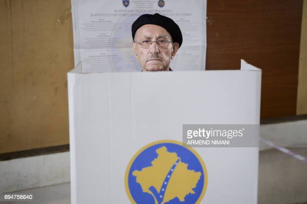 A man prepares to fill out his ballot paper at the polling station in Pristina on June 11 2017 during early parliamentary elections in Kosovo / AFP...