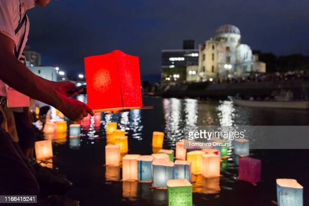 A man prepares to float a candle lit paper lantern on the river during an event to commemorate the 74th anniversary of the atomic bombing of...