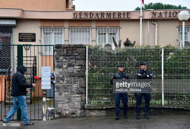 A man prepares to lay a flower as two gendarmes stand guard in front of the Gendarmerie Nationale in Carcassonne on March 24 2018 in tribute to a...