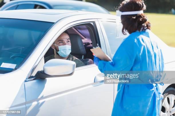 男はcovid-19テストを受ける準備をします - ドライブスルー検査 ストックフォトと画像
