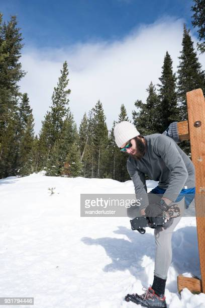 Man prepares to run on snowy trails in forest