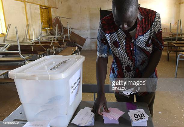 A man prepares to vote at a polling station in Fatick on March 20 2016 as part of a referendum on sweeping constitutional reforms including cutting...