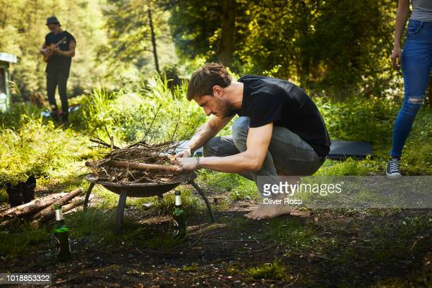 man preparing a campfire in a brazier - firewood stock pictures, royalty-free photos & images