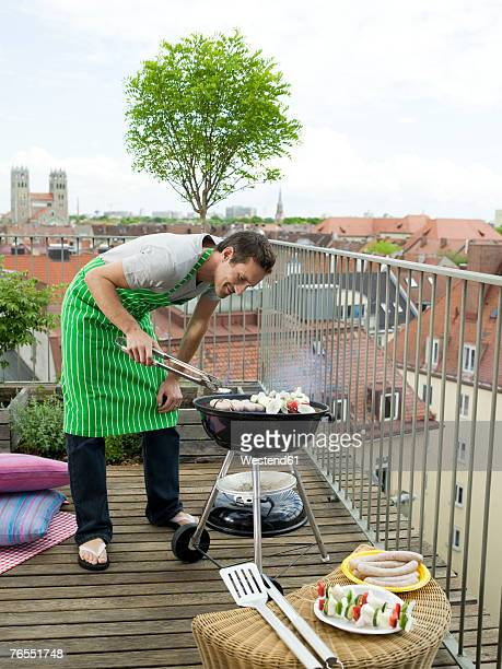 Man preparing barbecue on balcony, smiling