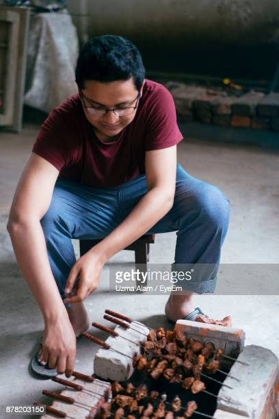 Man Preparing Barbecue On Grill While Sitting Indoors