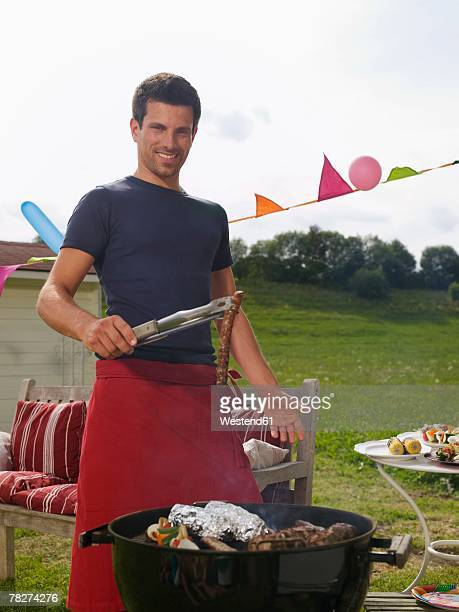 Germany, Bavaria, Man barbecuing in garden, smiling