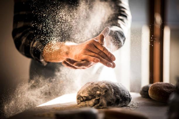 man preparing black burger buns in kitchen - 焗 預備食物 個照片及圖片檔