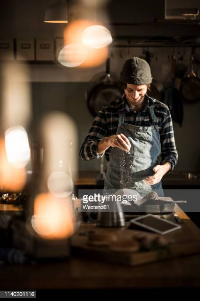 man preparing bread dough in his kitchen - kochen stock-fotos und bilder